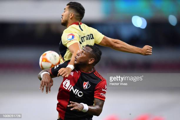 Leiton Jimenez of Atlas struggles for the ball with Henry Martin of America during the second round match between Club America and Atlas as part of...