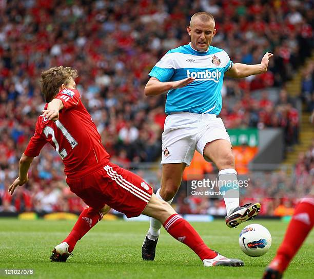 Leiva Lucas of Liverpool tackles Lee Cattermole of Sunderland during the Barclays Premier League match between Liverpool and Sunderland at Anfield on...