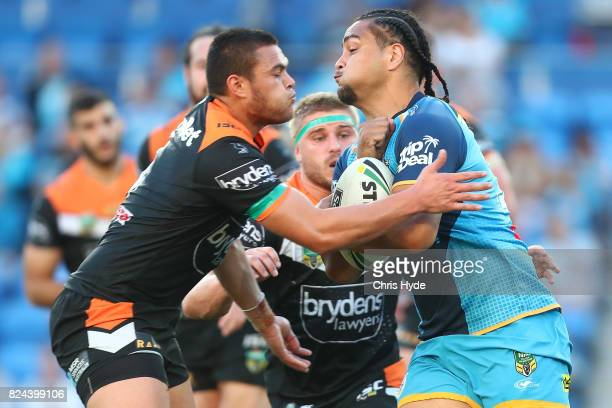 Leivaha Pulu of the Titans is tackled by Tuimoala Lolohea of the Tigers during the round 21 NRL match between the Gold Coast Titans and the Wests...