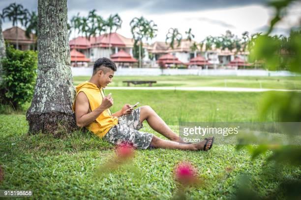 Lelaki muda Thailand mendengar senarai main kegemarannya di luar rumah telefon pintar