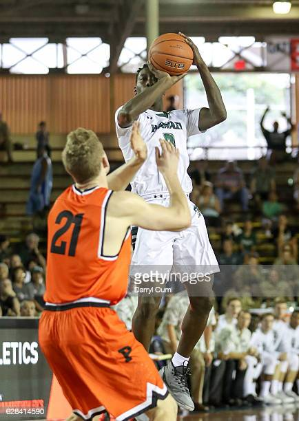 Leland Green of the Hawaii Rainbow Warriors shoots over Henry Caruso of the Princeton Tigers during the first half of the Pearl Harbor Invitational...