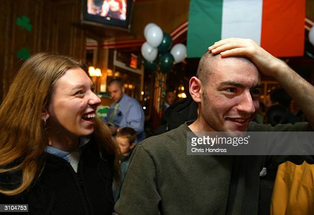 Lelena Cabsovich laughs while friend Mike Shub of Staten Island feels his head during a St Baldrick's Day event at Jim Brady's March 17 2004 in New...