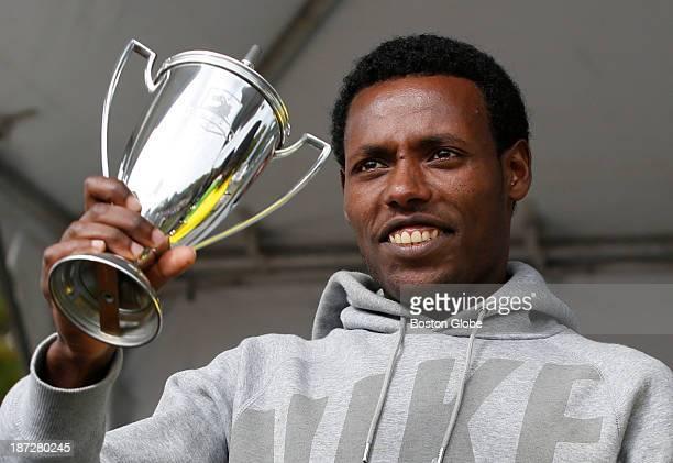 Lelisa Desisa of Ethiopia raises his trophy after winning the men's division of the BAA half marathon in Boston, Oct. 13, 2013.