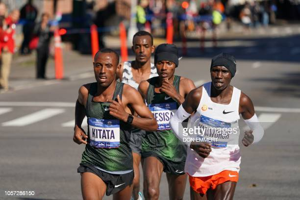 Lelisa Desisa of Ethiopia runs with Geoffrey Kamworor of Kenya and Ethiopian Shura Kitata during the Men's Division during the 2018 TCS New York City...