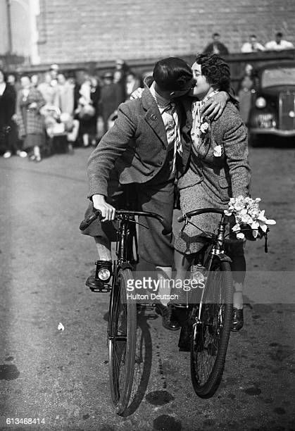 Lelise Seymour and Daisy Burgess exchange a kiss after their marriage at Hendon Registry Office before cycling to the Passport Office to collect the...