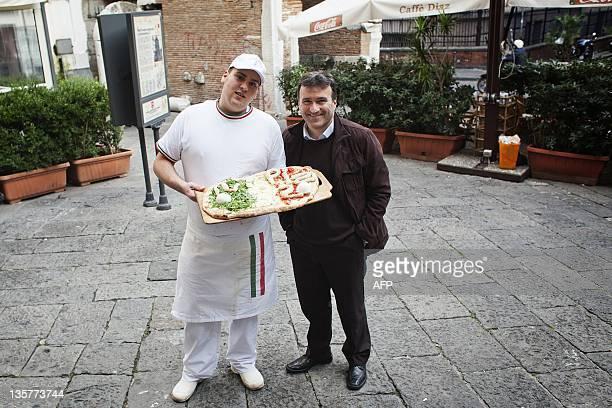 Lello Iovine of the antiracket association Pietrasanta poses togheter a pizzamaker in piazza Pietrasanta on December 13 2011 in Naples Butchers...