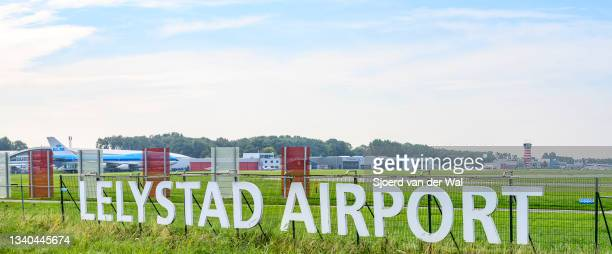 Lelystad airport sign in front of the runway with the air traffic control tower in the background on September 14, 2021 in Lelystad, The Netherlands....
