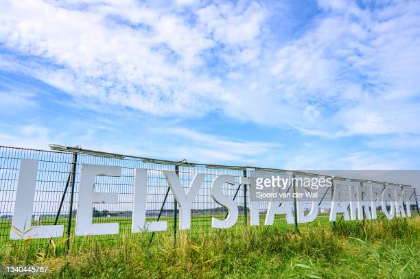 Lelystad airport sign in front of the runway with the new terminal for commercial flights in the background on September 14, 2021 in Lelystad, The...