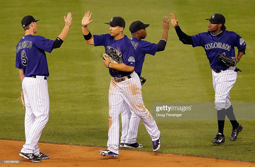 DJ LeMahieu #9, Carlos Gonzalez #5, Jonathan Herrera #18 and Eric Young Jr. #1 of the Colorado Rockies celebrate their 8-6 victory over the Milwaukee Brewers at Coors Field on August 14, 2012 in Denver, Colorado.