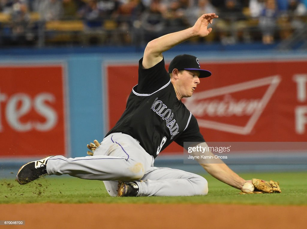 DJ LeMahieu #9 of the Colorado Rockies can't handle a single off the bat of Yasiel Puig of the Los Angeles Dodgers in the seventh inning of the game at Dodger Stadium on April 18, 2017 in Los Angeles, California.
