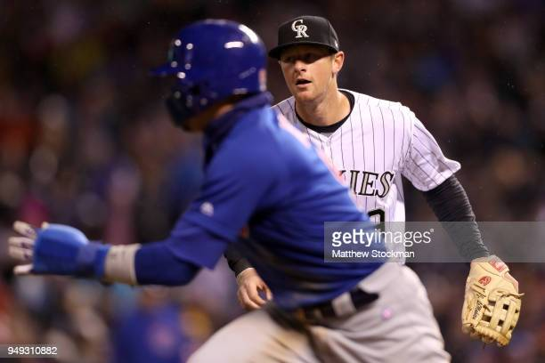 J LeMahieu of the Colorado Rockies chases down Javier Baez of the Chicago Cubs between third base and home plate for an out in the sixth inning at...
