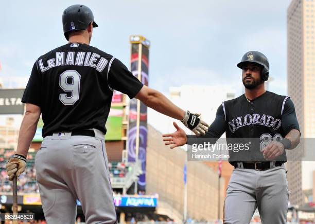 LeMahieu of the Colorado Rockies congratulates teammate Ian Desmond on scoring a run against the Minnesota Twins during the second inning of the game...