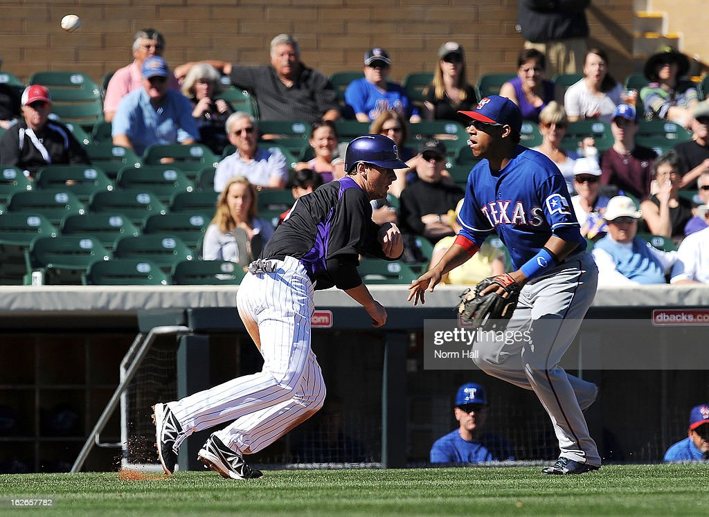 DJ LeMahieu #9 of the Colorado Rockies gets caught in a run down by Yangervis Solarte #63 of the Texas Rangers at Salt River Field on February 25, 2013 in Scottsdale, Arizona.