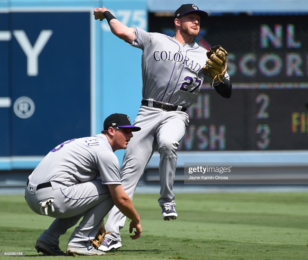 DJ LeMahieu #9 of the Colorado Rockies gets out of the way as Trevor Story #27 of the Colorado Rockies fails to throw Curtis Granderson #6 of the Los Angeles Dodgers out at first base in the second inning of the game at Dodger Stadium on September 10, 2017 in Los Angeles, California.