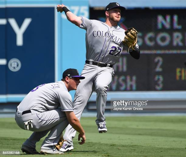 LeMahieu of the Colorado Rockies gets out of the way as Trevor Story of the Colorado Rockies fails to throw Curtis Granderson of the Los Angeles...