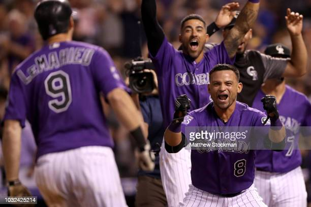 J LeMahieu of the Colorado Rockies is congratulated at the plate by Gerardo Parra and his teammates after hitting a walk off 2 RBI home run in the...