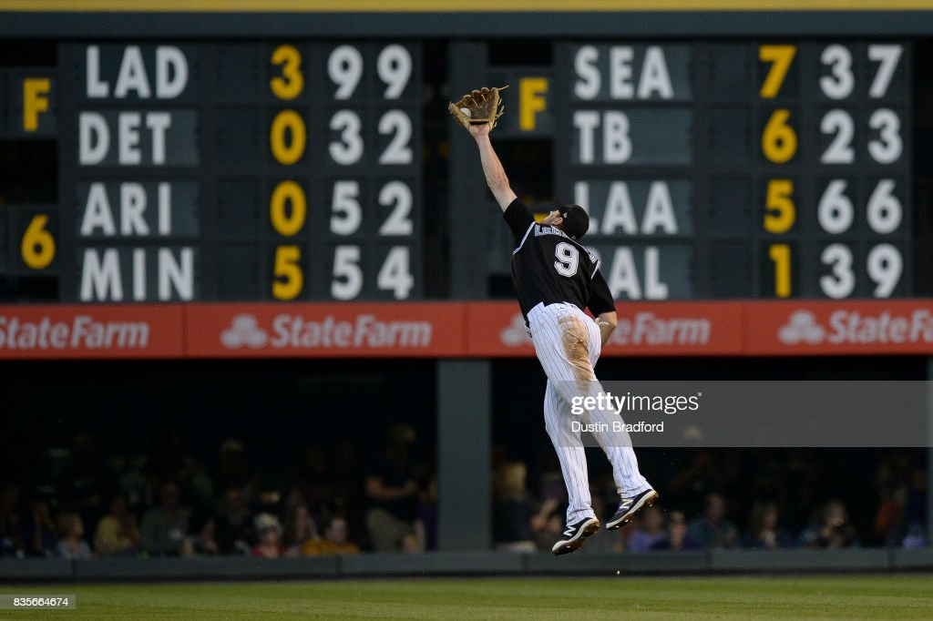 DJ LeMahieu #9 of the Colorado Rockies makes an acrobatic defensive play for an out in the fifth inning of a game against the Milwaukee Brewers at Coors Field on August 19, 2017 in Denver, Colorado.