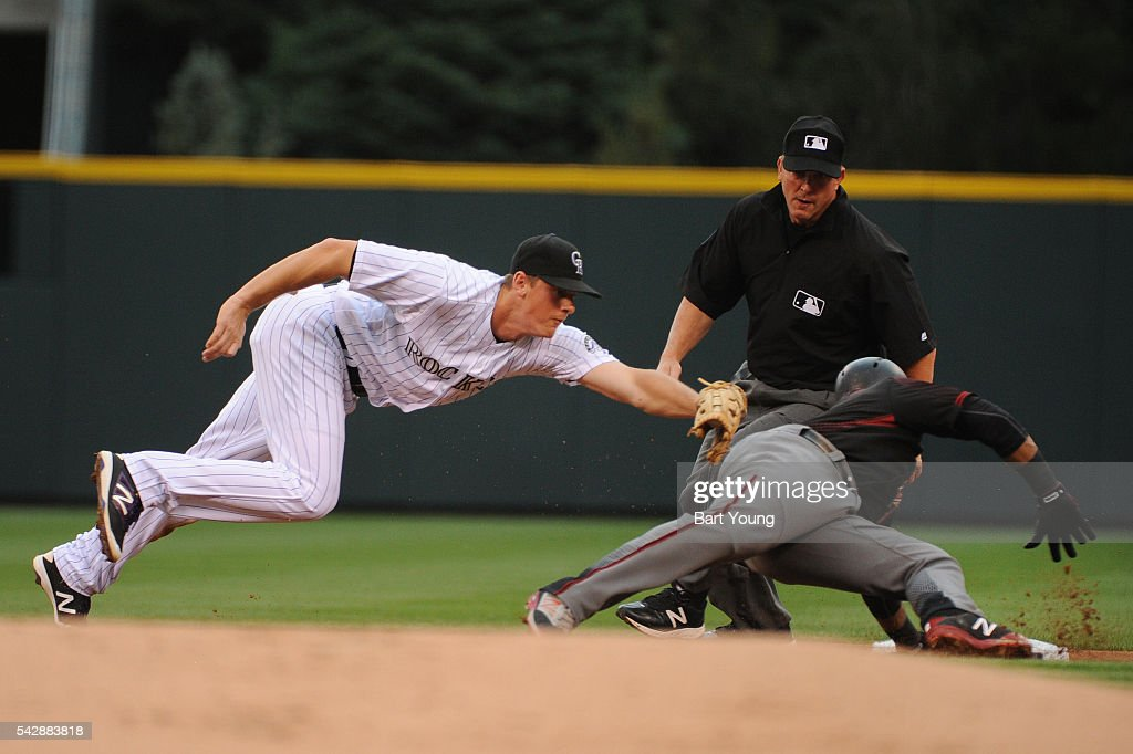 DJ Lemahieu #9 of the Colorado Rockies misses the tag in the first inning against Jean Segura #2 of the Arizona Diamondbacks at Coors Field on June 24, 2016 in Denver, Colorado.
