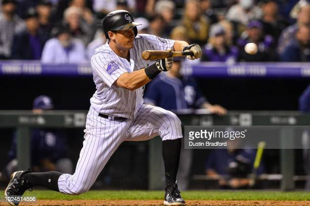 LeMahieu of the Colorado Rockies puts down a sacrifice bunt against the San Diego Padres in the eighth inning of a game at Coors Field on August 21...