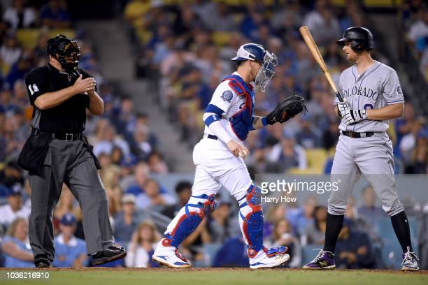 LeMahieu of the Colorado Rockies reacts to his strikeout in front of Yasmani Grandal of the Los Angeles Dodgers and umpire Tony Randazzo during the...
