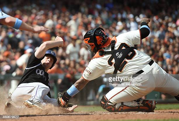 LeMahieu of the Colorado Rockies scores the goahead run beating the tag of catcher Hector Sanchez of the San Francisco Giants in the top of the...