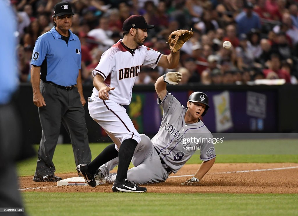 DJ LeMahieu #9 of the Colorado Rockies slides safely into third base after hitting a triple as Adam Rosales #9 of the Arizona Diamondbacks waits for the throw from center field during the eighth inning at Chase Field on September 11, 2017 in Phoenix, Arizona.