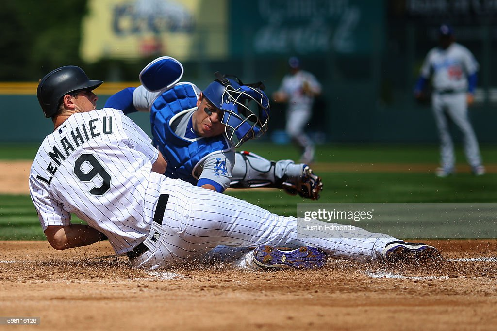 DJ LeMahieu #9 of the Colorado Rockies slides to score ahead of the tag from catcher Carlos Ruiz #51 of the Los Angeles Dodgers on a double off the bat of Nolan Arenado during the first inning at Coors Field on August 31, 2016 in Denver, Colorado.