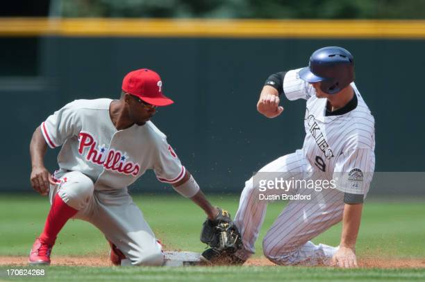 LeMahieu of the Colorado Rockies steals second base ahead of a tag attempt by Jimmy Rollins of the Philadelphia Phillies in the first inning of a...