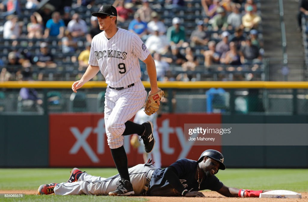 DJ LeMahieu #9 of the Colorado Rockies steps over Brandon Phillips #4 of the Atlanta Braves after Philips reached second base in the seventh inning on a single hit by Nick Markakis #22 of the Atlanta Braves at Coors Field on August 17, 2017 in Denver, Colorado.