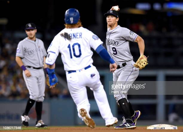 LeMahieu of the Colorado Rockies throws over Justin Turner of the Los Angeles Dodgers for a double play during the sixth inning at Dodger Stadium on...