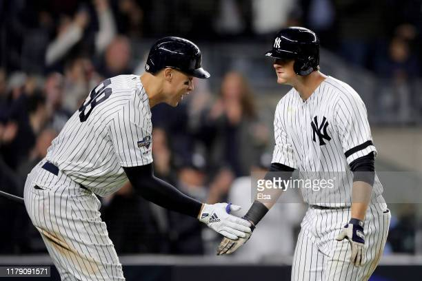 LeMahieu of the New York Yankees celebrates with teammate Aaron Judge after scoring a solo home run against Cody Stashak of the Minnesota Twins...