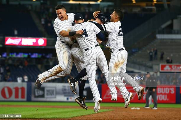 LeMahieu of the New York Yankees is mobbed by his teammates after hitting a gamewinning single in the bottom of the ninth inning against the Seattle...
