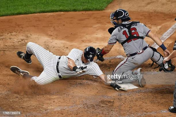 LeMahieu of the New York Yankees slides safely into home as Travis d'Arnaud of the Atlanta Braves is late with the tag in the fourth inning at Yankee...