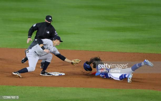 LeMahieu of the New York Yankees tags out Bo Bichette of the Toronto Blue Jays as he tries to steal second base at Sahlen Field on September 23 2020...