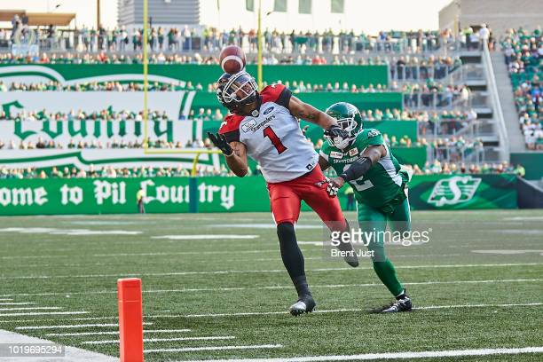 Lemar Durant of the Calgary Stampeders watches a ball sail just out of his reach while Jovon Johnson of the Saskatchewan Roughriders provides the...