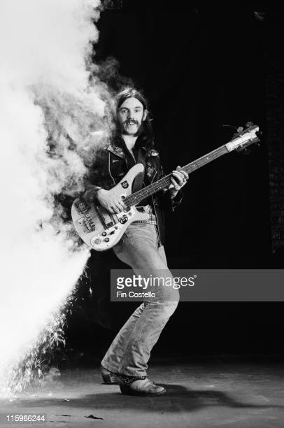 Lemmy Kilmister, British rock bassist and singer with British heavy metal band Motorhead, poses with his bass guitar with fireworks attached, firing...