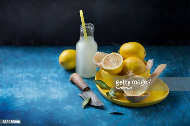 Lemon and juice on blue background.