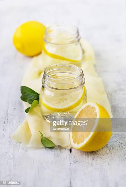 Lemon and lemon water in vintage glass jar.