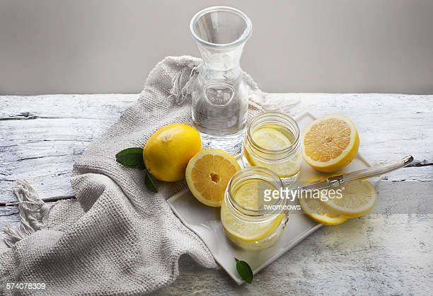 Lemon and lemon water on wooden table top.