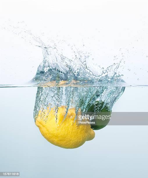 Lemon and lime splashing into the water