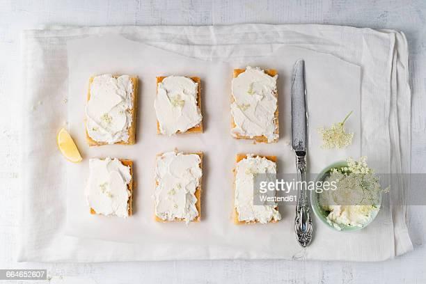 Lemon cake with elder curd cream, knife on baking paper