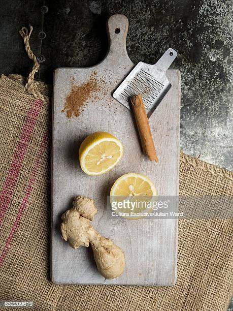 Lemon, cinnamon stick and fresh ginger on chopping board, overhead view