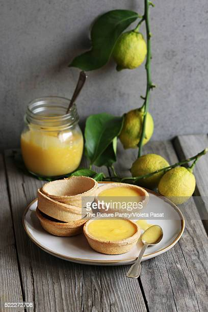 Lemon curd tarts and baked pastry on a plate and a jar of lemon curd and fresh lemon on background
