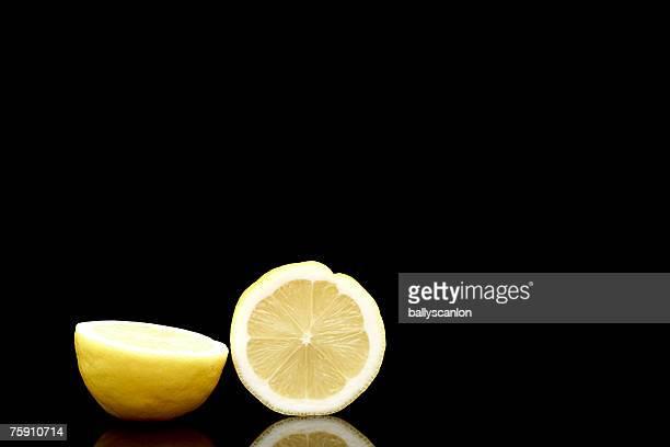 Lemon (citrus limon) cut in half on a black background