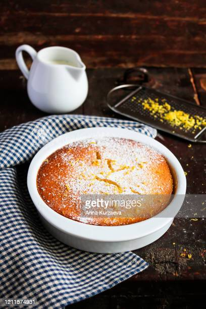 lemon delicious pudding dusted with powdered sugar in a baking bowl on a wooden table, selective focus - easter cake stock pictures, royalty-free photos & images