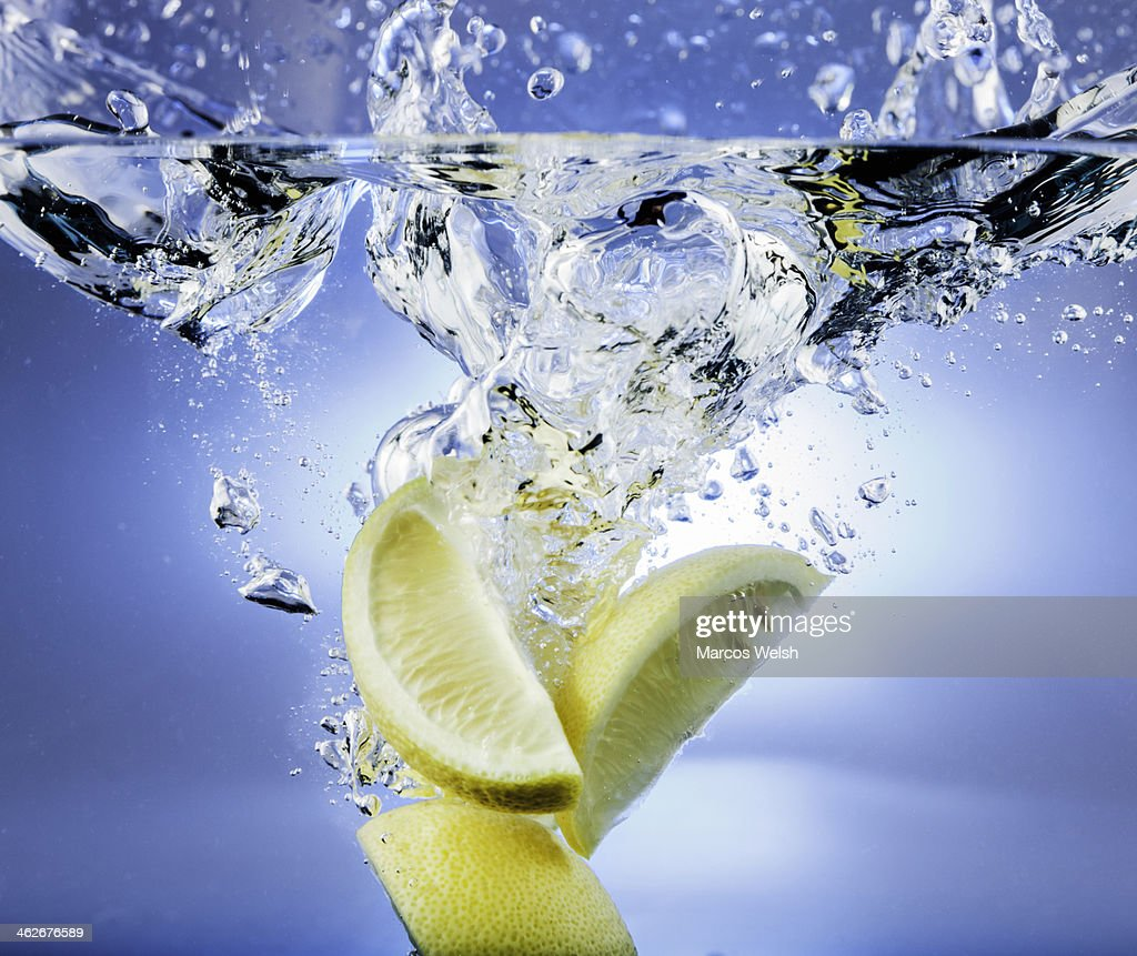 Lemon falling into water with splash : Stock Photo