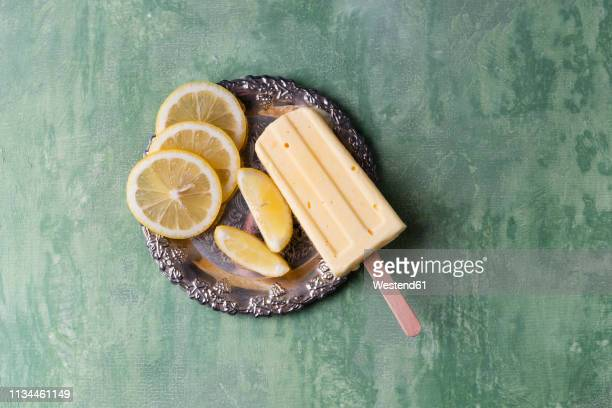 lemon ice lolly and lemon slices on silver plate - sour taste stock pictures, royalty-free photos & images