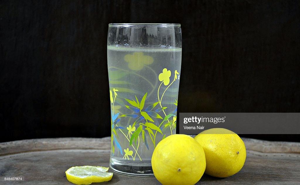 Lemon juice in a glass with lemons : Stock Photo
