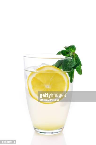Lemon juice with fresh mint leaf on white background