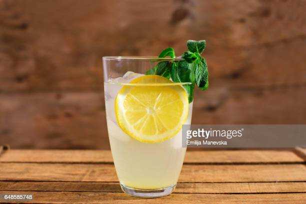 Lemon juice with fresh mint leaf on wooden background